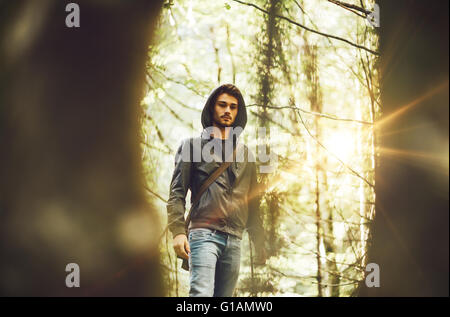 Young man walking in the forest framed by trees - Stock Photo