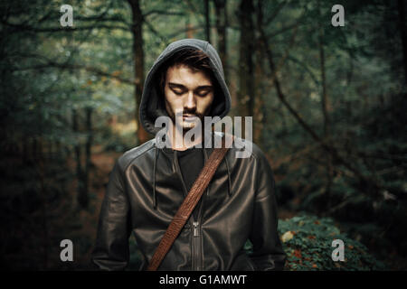 Young hooded cool man in the woods looking down, wild forest on background - Stock Photo