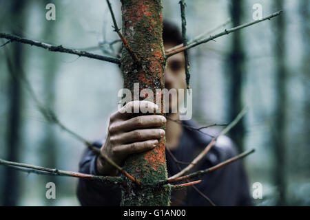Young man hiding in the woods and holding a trunk, hand on foreground, selective focus - Stock Photo