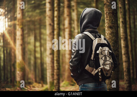 Young hooded man hiking in the woods, freedom and nature concept - Stock Photo