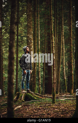 Hooded young man standing in the forest and exploring, freedom and nature concept - Stock Photo