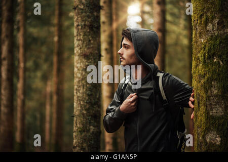 Young handsome man walking in a forest and looking around, nature and exploration concept - Stock Photo
