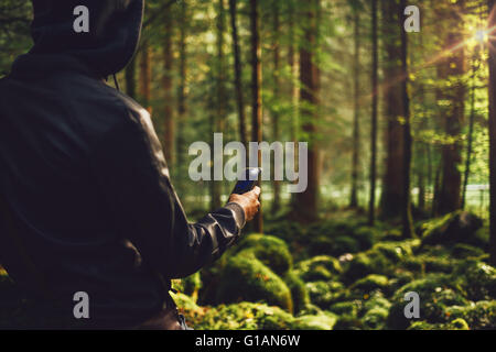 Hooded man in the woods taking pictures with a mobile phone, trees and moss covered rocks on background - Stock Photo