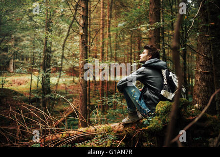 Young man sitting on a trunk in the forest and relaxing, freedom and individuality concept - Stock Photo