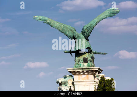 Mythical Turul Bird bronze staute by (Gyula Donáth, 1905) against a blue sky with cumulus clouds in the Castle Hill - Stock Photo
