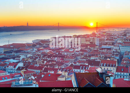 Lisbon cityscape with the sun in the sky at sunset. Portugal - Stock Photo