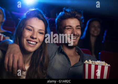 Happy young couple in the movie theater watching a film and smiling, entertainment and togetherness concept - Stock Photo