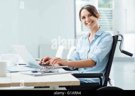 Confident happy businesswoman in wheelchair working at office desk and using a laptop, she is smiling at camera, - Stock Photo
