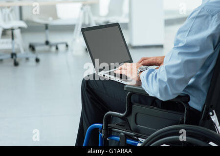 Corporate businessman in wheelchair using a laptop and networking, unrecognizable person - Stock Photo