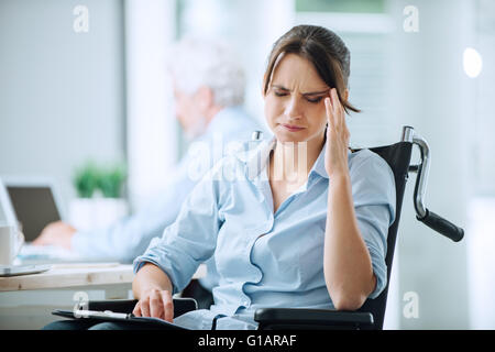Disabled business woman in wheelchair at office having an headache touching her temples - Stock Photo