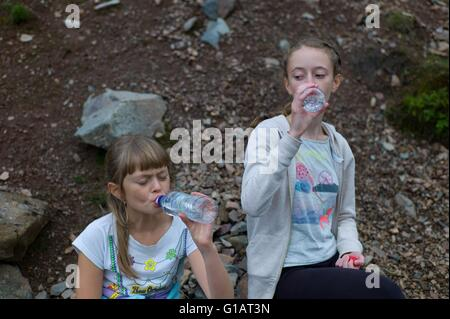 Tired children drinking water on a walk in the Lake District Cumbria UK