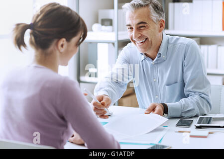 Young woman having a business meeting and signing a contract, recruitment and agreement concept - Stock Photo