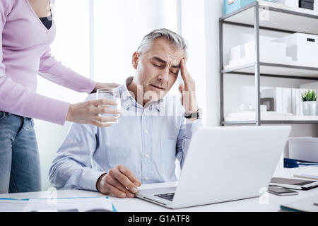 Tired businessman in the office working at desk and having a bad headache, his colleague is giving him a glass of - Stock Photo