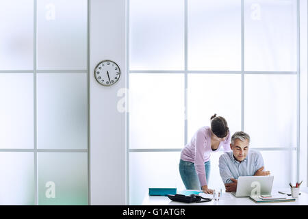 Executive working at office desk with his assistant, they are using a laptop and connecting to internet - Stock Photo
