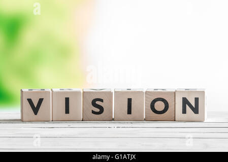 Vision sign made of wooden cubes on a desk - Stock Photo