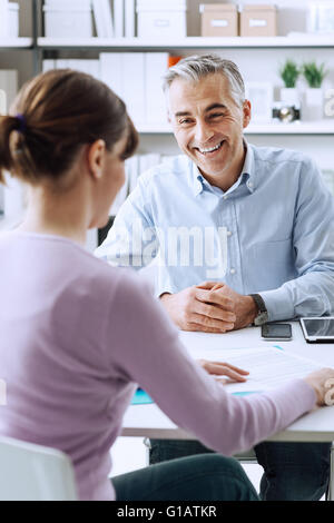 Mature businessman and young woman having a business meeting in the office, they are discussing together - Stock Photo