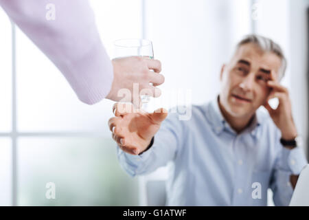 Exhausted businessman working in his office and having a headache, his assistant is handing him a glass of water, - Stock Photo