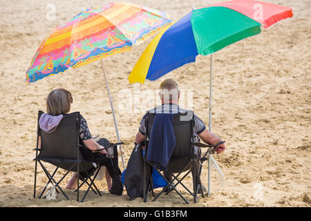 Bournemouth, Dorset, UK 12 May 2016. Couple relaxing on Bournemouth beach under colourful parasols  Credit:  Carolyn - Stock Photo