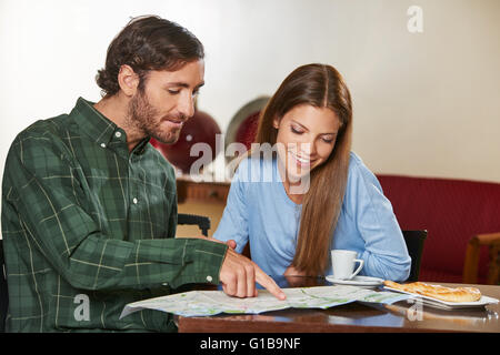Couple in hotel looking at city map during their vacation - Stock Photo