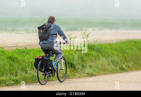 Cyclist cycling alone on a country road in the UK. Healthy lifestyle. - Stock Photo