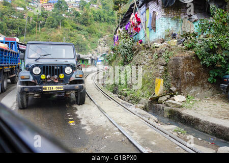 A Mahindra Jeep on National Highway 55 standing besides the Darjeeling Himalayan Railway Toy Train track. - Stock Photo