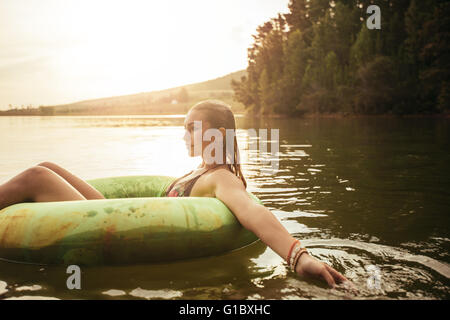 Side portrait of young woman in lake on inflatable ring. Woman relaxing in water on a summer day. - Stock Photo