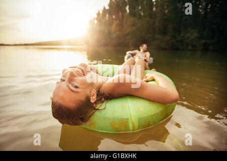 Closeup portrait of smiling young girl floating in an innertube with a man at the background in a lake. Young woman - Stock Photo