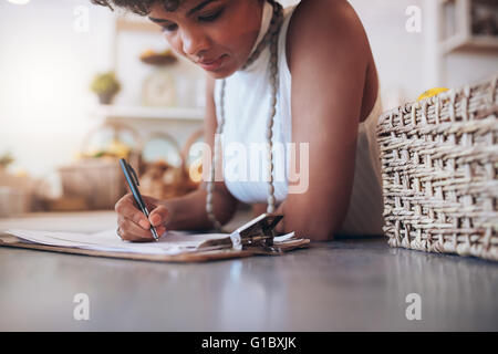 Cropped image of young african woman working in a juice bar. Female standing behind the counter and writing notes. - Stock Photo