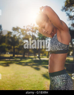 Side view image of fit young woman exercising at the park. Healthy female with strong six-pack doing morning workout - Stock Photo