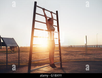 Full length shot of fit young woman in sportswear exercising on wall bars outdoors during sunset. Fitness woman - Stock Photo
