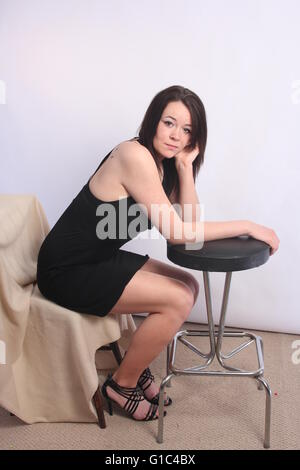 Pretty young brunette, sitting, wearing a  short black dress. - Stock Photo