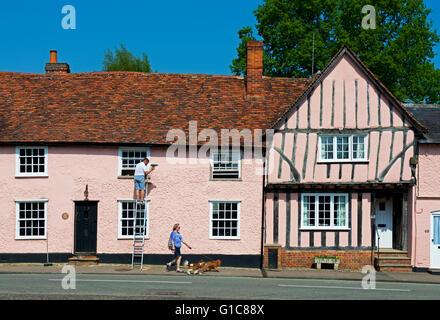 Man on ladder, repairing window frames on house in the village of Lavenham, Suffolk, England UK - Stock Photo