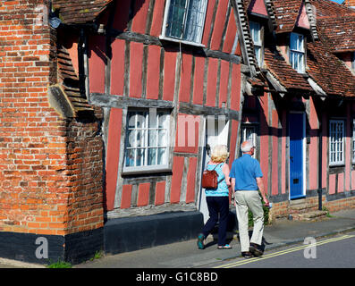 Couple walking past medieval half-timbered houses in the village of Lavenham, Suffolk, England UK - Stock Photo