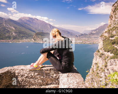 Young sporty woman admire the panorama from the Ponale trail in Riva del Garda, Italy. - Stock Photo