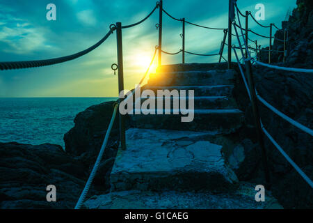 Stairways in rock over sea at sunset - Stock Photo
