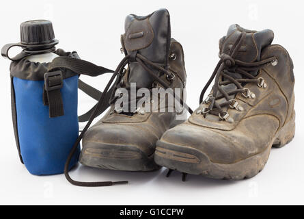 Close up of dusty worn hiking boots with water bottle on white - Stock Photo