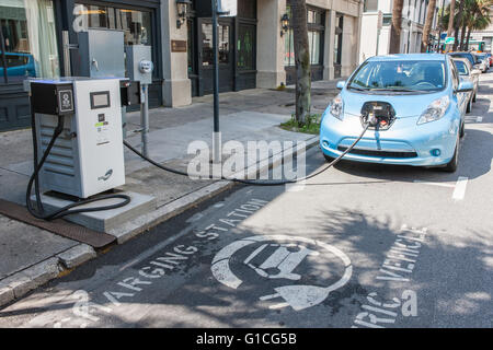 A Nissan Leaf electric car gets a charge from a public SigNet charging station on Bull Street in Savannah, Georgia. - Stock Photo