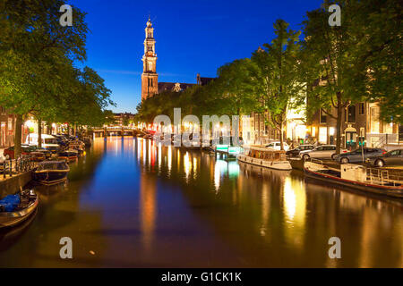 Western church reflecting in water of Prinsengracht canal in Amsterdam - Stock Photo