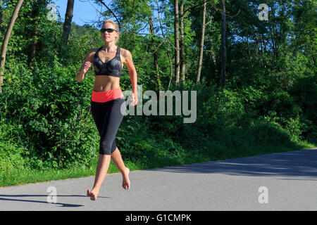 A blonde woman running barefoot - Stock Photo