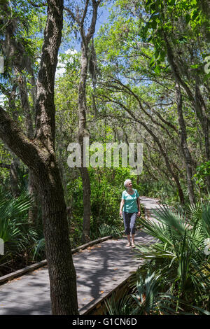 Titusville, Florida - A woman walks on a boardwalk trail in Merritt Island National Wildlife Refuge. - Stock Photo