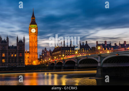 Long exposure at dusk of buses on Westminster Bridge and boats on the River Thames, London, UK. - Stock Photo