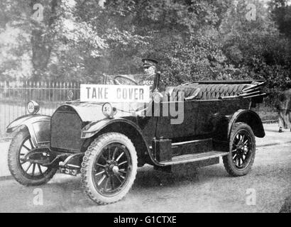 First World War air raid warden driving a car with a warning card saying 'take cover' during a German air raid in - Stock Photo