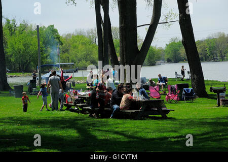 Group of people picnicking at riverside park. - Stock Photo