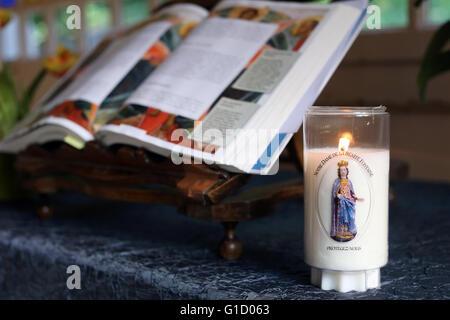 Sanctuary of La Benite Fontaine. Church candle and open bible.  La Roche-sur-Foron. France. - Stock Photo