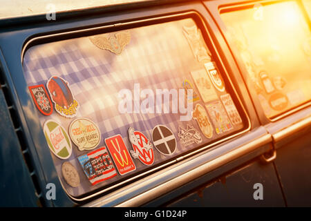 Stickers in the window of a VW Campervan with added nostalgic filter and dusky sun flare - Stock Photo