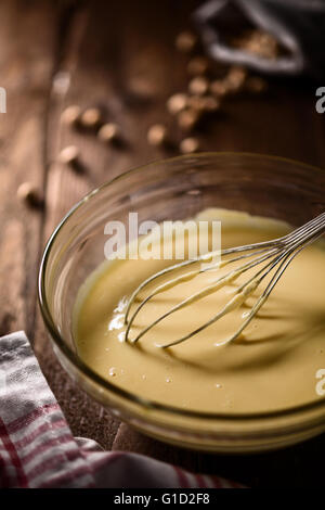 Chickpea Batter in a Bowl with a Whisk on Wood - Stock Photo