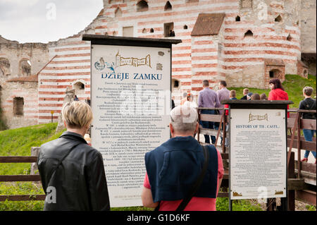 History of the Janowiec Castle, people reading the visitor information board in front of the bridge to historical - Stock Photo