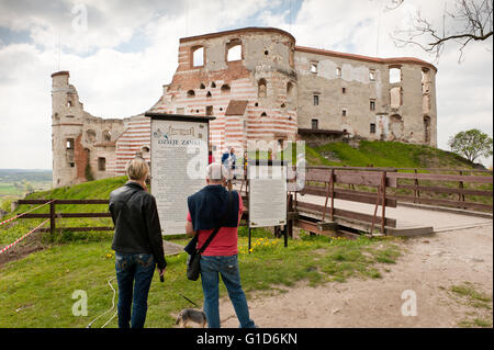 Janowiec Castle exterior and people reading about history on the visitor information board in front of the bridge - Stock Photo