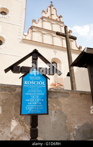 Informational church cross in Janowiec village, Poland, Europe, blue board with mass schedule information in front - Stock Photo