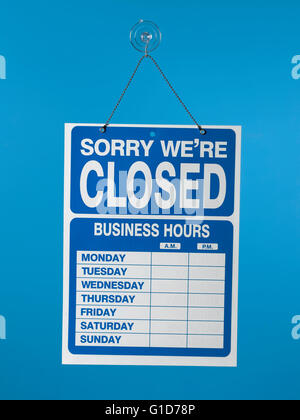 blank shop sign closed hanging on a blue background - Stock Photo